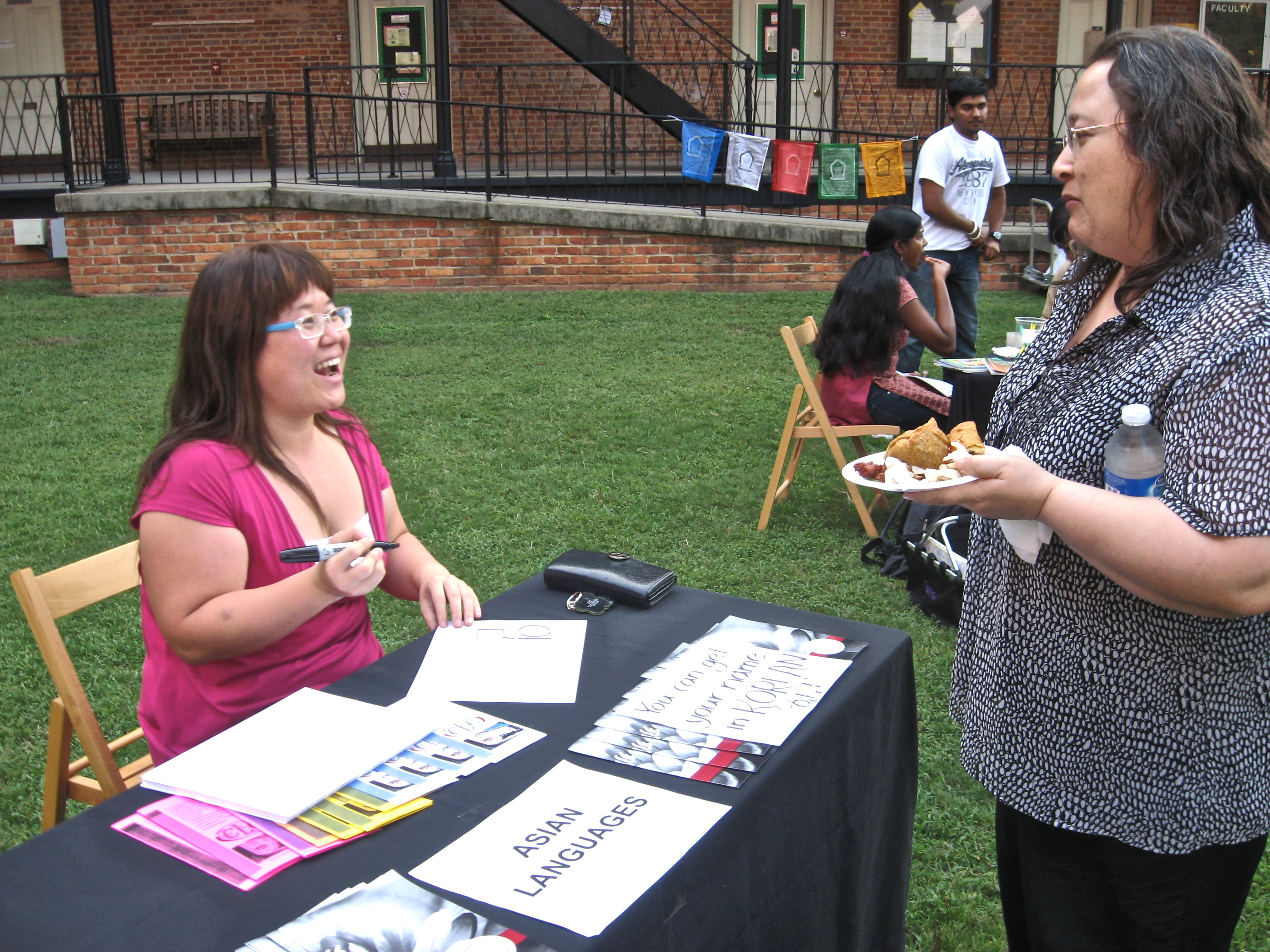 student talking with professor at Asian Languages table