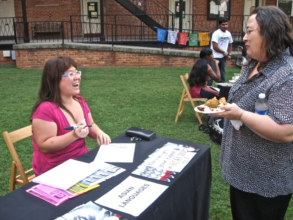 Student and professor talking at Asian Languages table outside Manly Hall